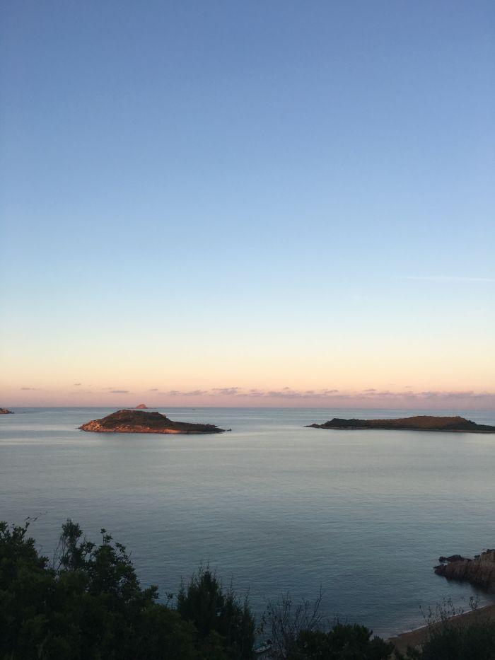 Západ sluníčka nad pláží Capo Coda Cavallo